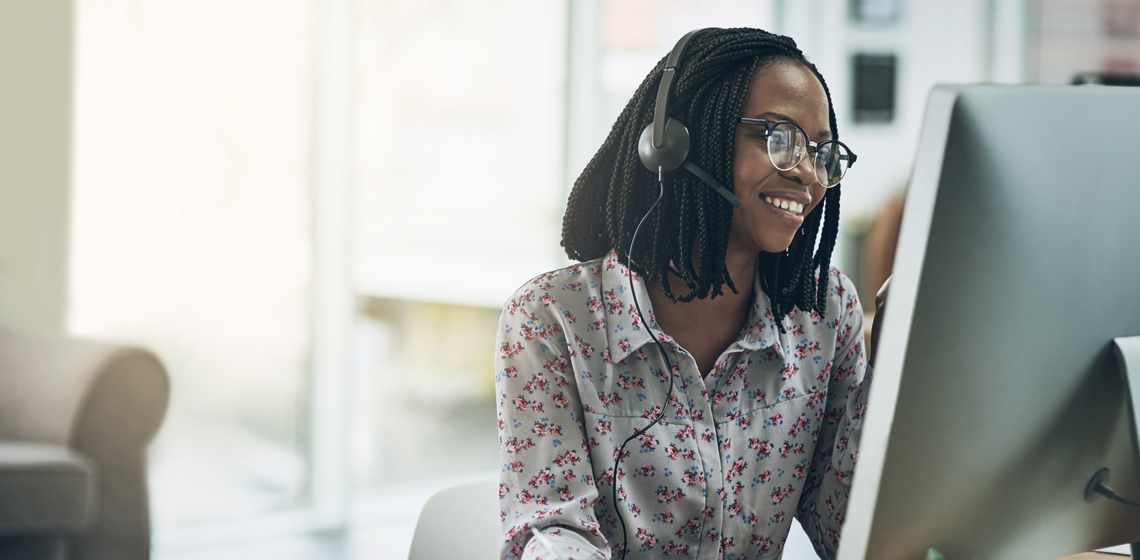 Woman working in an office with a headset.