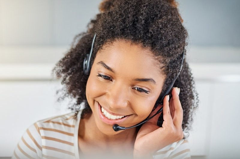 A woman talking on a headset.