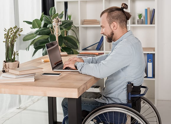 Employee working on a laptop from his wheelchair.