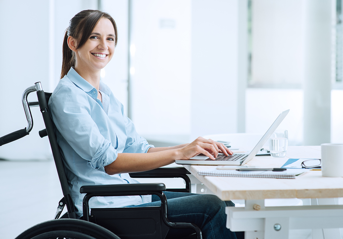 Employee working on a laptop from her wheelchair.